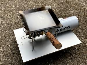 フィールドホッパーの上にレギュレーターストーブを置いて、グリップを付けたフライアンを置いてみたの図(シーズニング中)