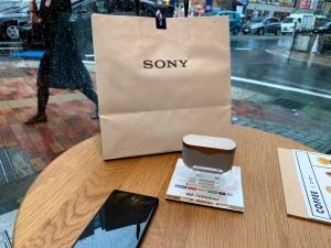 雨のSONYストア福岡天神で、紙袋を通行人に見えるように置いてくつろぐ私。
