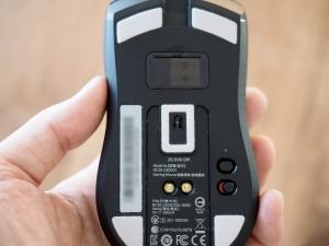 マウス底面。中央の白い四角がセンサー部、その上がUSBドングルの格納スペース。下の二つ並んだ金色の〇が充電端子。右下のスイッチは上から感度変更と電源です。